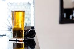 E-cigarette lying alongside beer and a camera Stock Image