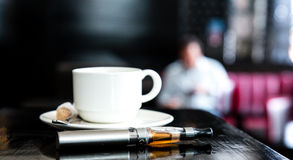 E-cigarette lying on a bar counter with coffee Royalty Free Stock Image