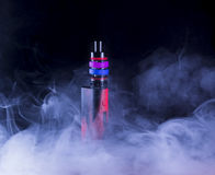 E-cigarette in smoke. On black background Royalty Free Stock Image