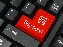 E-commerce. Closeup of red computer keyboard key with shopping cart symbol and Buy Now text Royalty Free Stock Images