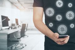 E-commerce and banking concept. Close up of man hand holding smartphone with creative bitcoins on blurry office interior background. E-commerce and banking Royalty Free Stock Photo