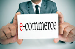 E-commerce. A businessman sitting in a desk holding a signboard with the word e-commerce written in it Stock Photos