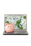 E-commerce concept. Piggy bank and computer with money's screen royalty free stock photos