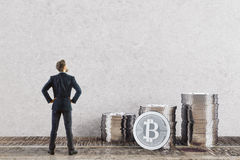 E-commerce concept. Back view of young businessman looking at silver bitcoin piles in room with concrete wall and wooden floor. E-commerce concept. 3D Rendering royalty free stock photos