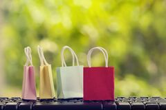E-Commerce concept. : Color paper shopping bags with on notebook keyboard in the natural green background. International freight