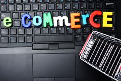 E-commerce concept with colorful letter blocks and shopping trolley on notebook keyboard Royalty Free Stock Photography