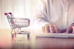 E-commerce concept. Man`s hands typing on computer keyboard next to a shopping cart. Concept of online shopping and e-commerce, for background, website banner stock images