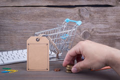 E-commerce concept. Purchasing cart with a blank price tag on a dark wooden background.  Stock Image