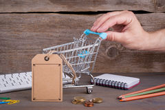 E-commerce concept. Purchasing cart with a blank price tag on a dark wooden background.  Royalty Free Stock Image