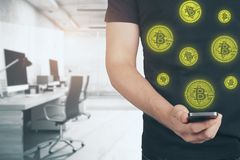 E-commerce and currency exchange concept. Close up of man hand holding smartphone with creative bitcoins on blurry office interior background. E-commerce and Royalty Free Stock Images
