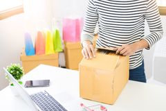 E-commerce delivery concept and online selling start up small bu. Siness owner packing in the card box at workplace. freelance woman seller prepare product for royalty free stock photos