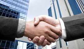 E-commerce hand shake. With modern buildings as background Royalty Free Stock Photo