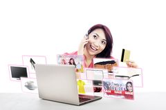 E-commerce and Online Shopping. An attractive women purchasing product online using her laptop computer, credit card, and mobile phone Royalty Free Stock Photography