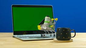 E-commerce shopping concept with miniature shopping cart and modern laptop. stock photography