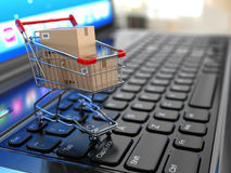 E-commerce. Shopping cart with cardboard boxes on laptop. Royalty Free Stock Images