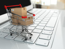 E-commerce. Shopping cart with cardboard boxes on laptop. Royalty Free Stock Image