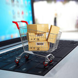 E-commerce. Shopping cart with cardboard boxes on laptop. Royalty Free Stock Photography