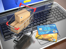 E-commerce. Shopping cart and credit cards on laptop. Royalty Free Stock Photos