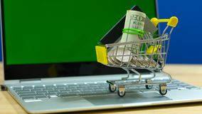 E-commerce shopping concept with miniature shopping cart and modern laptop. E-commerce retail shopping concept with miniature shopping cart and modern laptop stock images