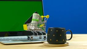 E-commerce shopping concept with miniature shopping cart and modern laptop. royalty free stock images