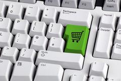 E-commerce shopping trolley button. Shopping cart icon button on the enter key of a computer keyboard Stock Photography