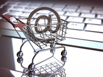 E Commerce. At sign, inside of the shopping cart on a laptop. E commerce concept. Depth of field with focus on At sign Stock Photos