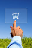 E-commerce solutions. Hand touching a screen with a shopping cart, e-commerce solutions concept Royalty Free Stock Photos
