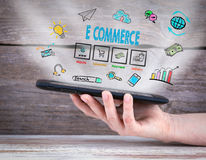E commerce. Tablet computer in the hand. Old wooden background Stock Photos