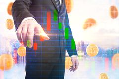 E-commerce and trade concept. Businessman pointing at abstract forex chart on city background with bitcoin rain. E-commerce and trade concept. Double exposure Stock Image
