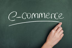 E-commerce. Woman hand writing E-commerce on chalkboard Stock Image