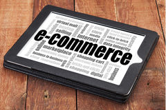 E-commerce word cloud. A digital tablet on a rustic wooden table Royalty Free Stock Image