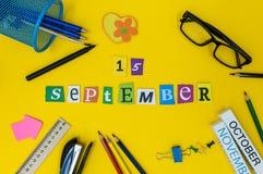 E Dag 15 av månaden, tillbaka till skolabegreppet Kalender på lärare- eller studentarbetsplatsbakgrund med skolan Arkivfoton