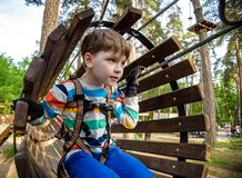 E De vakantieconcept van de zomer Weinig jongen die bij het park van het kabelavontuur spelen modern stock afbeelding