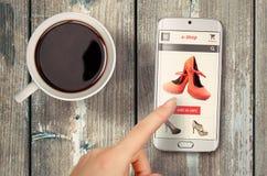 E-Einkaufen mit intelligentem Telefon auf Tabelle lizenzfreie stockfotos