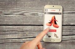 E-Einkaufen mit intelligentem Telefon auf Tabelle stockfoto
