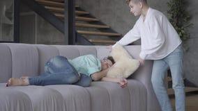 E El hijo adolescente pone la almohada bajo cabeza de la mujer y después miente cerca de mamá La mujer est? cansada almacen de metraje de vídeo