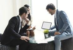 E El sentarse de la gente joven discute sobre nuevo proyecto de la estrategia sobre la sala de reuni?n fotografía de archivo libre de regalías