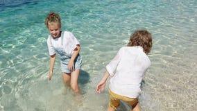 E Enfants heureux petit garçon joyeux et fille jouant en eau peu profonde Gar?on et filles s'asseyant sur le bureau surfant et le clips vidéos