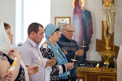 E folket rymmer stearinljus under ritualen av dopet i den ortodoxa kyrkan royaltyfri bild