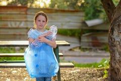 E Freiwilliges Kind mit einer Abfalltasche, welche die Sänfte, Plastikflasche in die Wiederverwertung der Tasche einsetzend aufrä lizenzfreie stockbilder