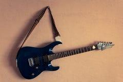 E-Gitarre auf einem Hintergrund der Weinlesebeigewand Stockfotografie