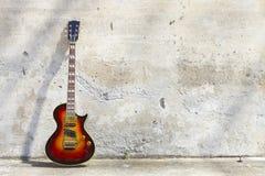 E-Gitarre vor einer Weinlesewand lizenzfreie stockfotografie