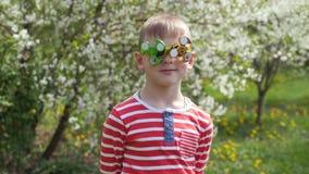 E gyckel p? gatan Ett barn på bakgrunden av att blomstra vita blommor av körsbäret stock video