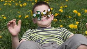 E gyckel p? gatan Pojke på en bakgrund av gula blommor, maskrosor arkivfilmer