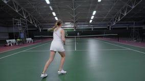 E Het mooie vrouwenspeler spelen met de mens in tennis stock footage