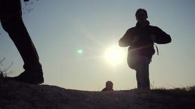 E hikers группы силуэта ног людей идя на верхнюю часть горы с акции видеоматериалы