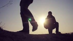 E Hikers группы силуэта ног людей идя на верхнюю часть горы с сток-видео