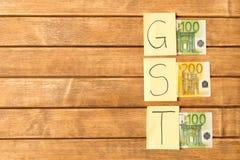 E impuesto de los bienes y servicios Inscripción de GST con los billetes de banco en woode fotografía de archivo libre de regalías