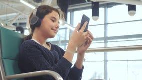 E jong gelukkig tienermeisje die in hoofdtelefoons aan de muziek luisteren stock video