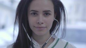 E Jonge donkerbruine vrouw die met lang haar in de stethoscoop van de cameraholding kijkt stock video